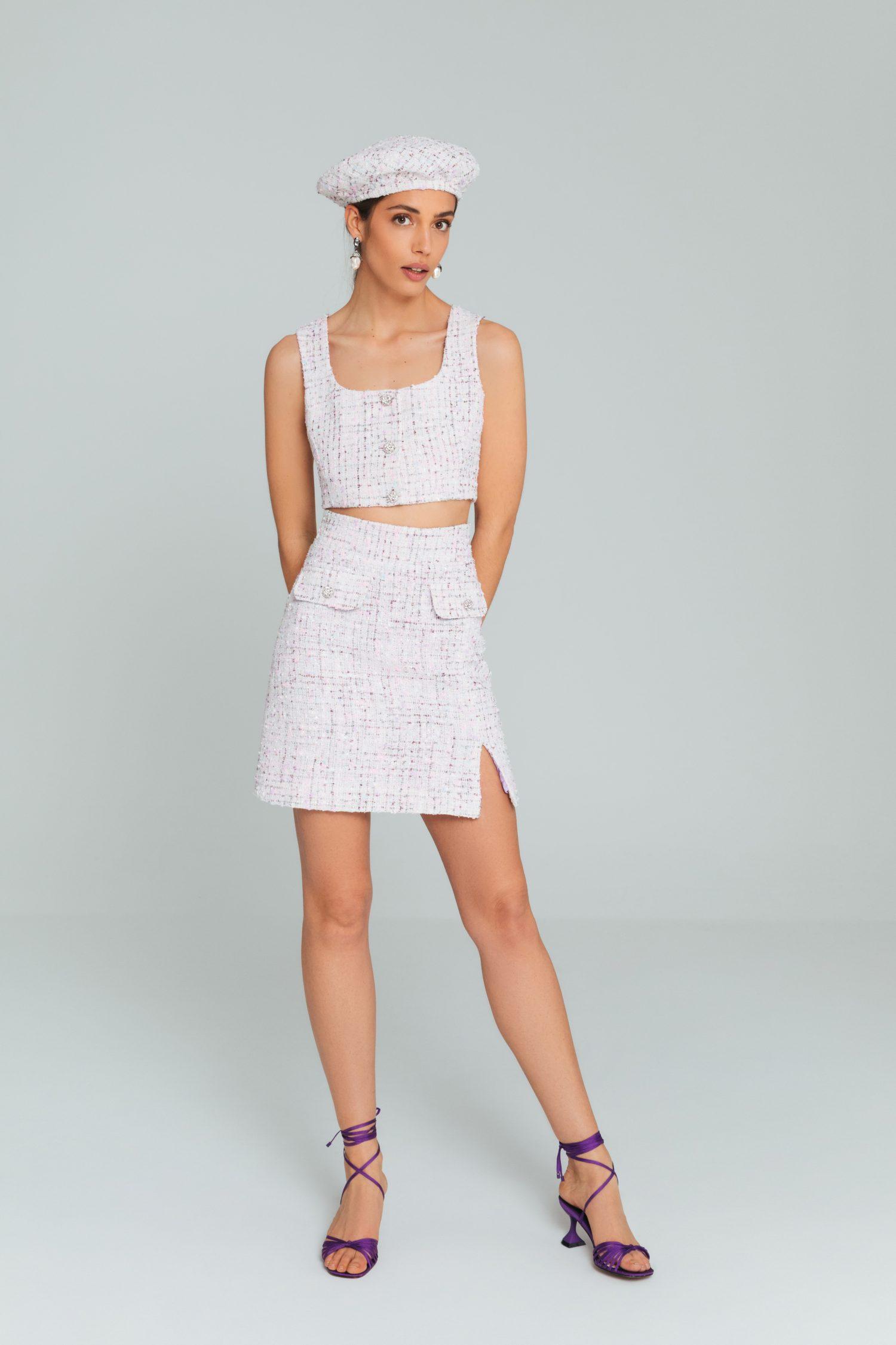 Modelo com boina, crop top e saia curta brancos em tweed da estilista Elsa Barreto.
